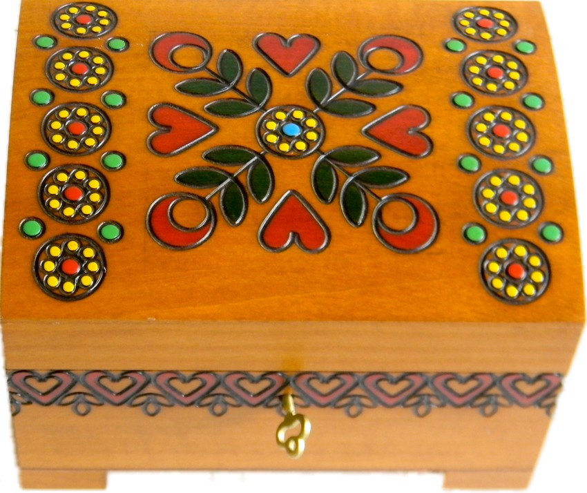 A beige wooden keepsake chest with lock and key with red hearts designs